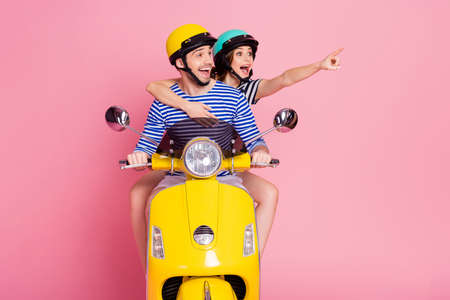Portrait of his he her she nice attractive cheerful amazed glad dreamy couple riding moped pointing forefinger far away cool tour rent insurance isolated on pink pastel color background