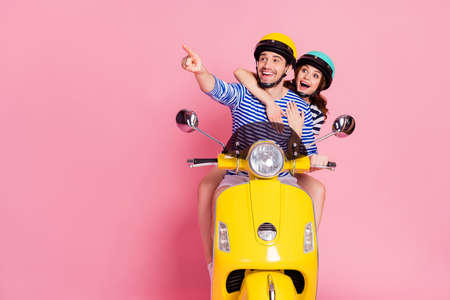 Portrait of his he her she nice attractive lovely cheerful cheery glad amazed couple riding moped having fun pointing forefinger copy space advert isolated on pink pastel color background