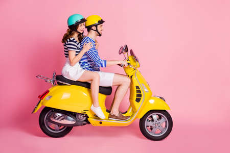 Profile side view portrait of his he her she nice attractive cheerful cheery couple riding moped having fun spending time traveling abroad isolated on pink pastel color background