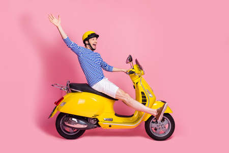 Profile side view of his he nice attractive handsome cheerful cheery crazy funky guy reckless driving moped having fun isolated over pink pastel color background