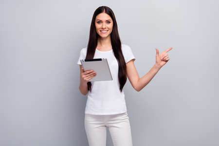 Portrait of her she nice attractive lovely charming cheerful cheery straight-haired girl holding in hands using ebook showing copy empty space isolated over light gray pastel color background