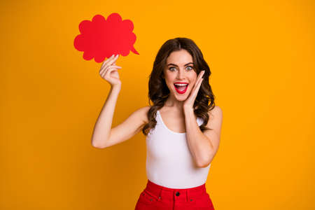Photo of funny cheerful lady hold paper mind cloud hand on cheek open mouth, recommending cool shopping wear white casual tank-top red skirt isolated yellow color background