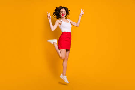 Full body profile photo of funny lady jump high good mood sunny day, weekend showing v-sign gesture wear white casual singlet red short skirt shoes isolated yellow color background