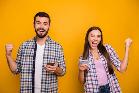 Photo funky lady handsome guy couple rejoicing astonished hold telephones read good news addicted popular bloggers wear casual plaid shirts outfit isolated yellow color background