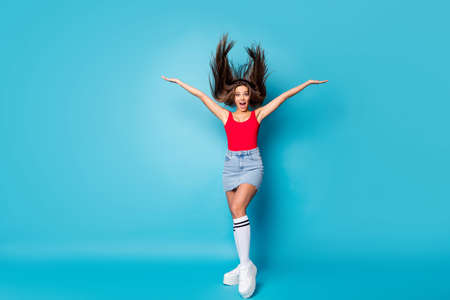 Full size photo of astonished cheerful positive girl impressed by strong spring wind her haircut fly throw hold hand scream wow omg wear singlet legs isolated over blue color background
