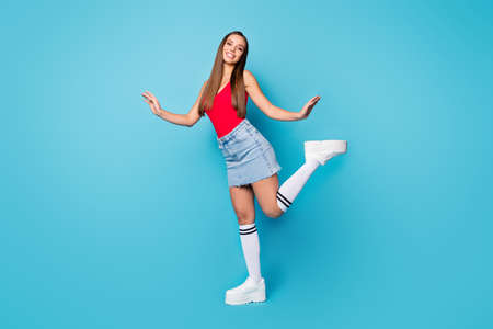 Full length photo of lovely girlish lady enjoy spring free time weekend holiday raise hands legs wear singlet shoes isolated over blue color background Foto de archivo