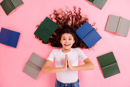 Top view above high angle flat lay flatlay lie concept portrait of her she nice funny cheerful wavy-haired girl different book asking favor isolated on pink pastel color background