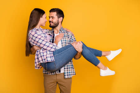 Photo of pretty lady handsome guy couple just married husband hold bride wife arms carry honeymoon car surprise trip journey wear casual plaid shirts jeans isolated yellow color background
