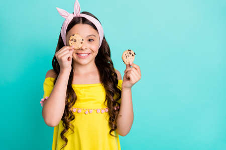 Portrait of positive girl child close cover eyes face chocolate cookies snack wear retro stylish, trendy yellow shirt dress isolated over teal color background