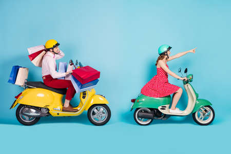 Full size profile photo of crazy shopaholic lady showing next store guy drive retro moped carry packs shopping abroad foreigners vintage clothes protective cap isolated blue color background