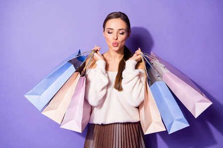 Portrait of romantic dreamy lovely charming girl hold many shopping bags she buy 14-ferbuary sales send air kiss wear white sweater isolated over purple color background