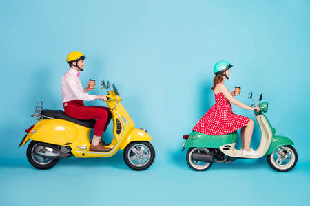 Full size profile photo of funny lady guy couple drive retro moped travelers drink takeaway coffee traffic jam good mood not rush vintage outfit protective cap isolated blue color background