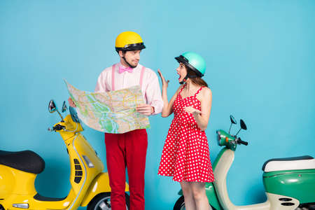 Photo of frustrated two people friends have argument ride drive scooters get lost cute girl scream guy read map wear red dress shirt isolated over blue color background
