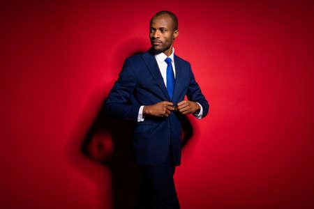 Photo of handsome attractive dark skin business guy look side buttoning blazer walking corporate meeting wear blue formalwear suit tuxedo isolated vivid red burgundy background 版權商用圖片
