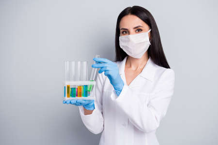 Close-up portrait of her she nice attractive girl biologist scientist expert doc holding in hands flasks analyzing creating remedy cure meds medical solution isolated over grey pastel color background