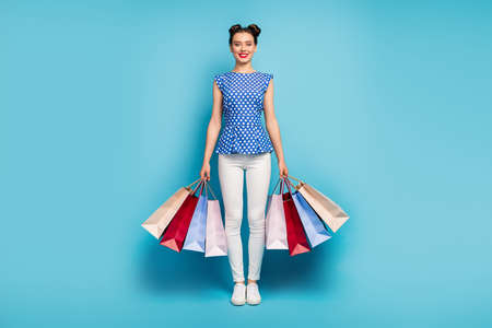 I wanna buy it all. Full body photo of pretty cheerful lady carry many packs addicted shopper wear dotted retro blouse white pants footwear isolated blue color background