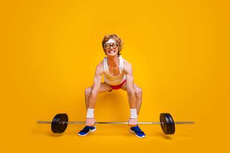 Full length body size view of his he nice funky slim motivated desperate foxy guy lifting barbell doing work out coacher program isolated over bright vivid shine vibrant yellow color background