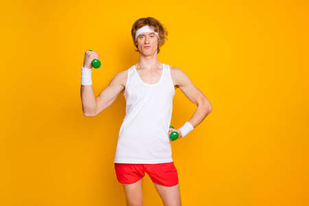Portrait of his he nice attractive funky focused arrogant content proud guy doing work out with small easy dumbbell endurance isolated over bright vivid shine vibrant yellow color background Foto de archivo