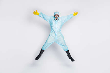 Full body photo medical man jump raise hands enjoy stop spread novel covid19 infection wear white suit biohazard yellow latex gloves goggles breathing mask isolated gray color background