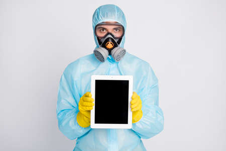 Portrait of medical worker man present tablet wear biohazard uniform breathing mask isolated over gray color background