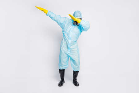 Full length photo of dabber man dance close cover face hands wear white biohazard uniform breathing mask isolated grey color background
