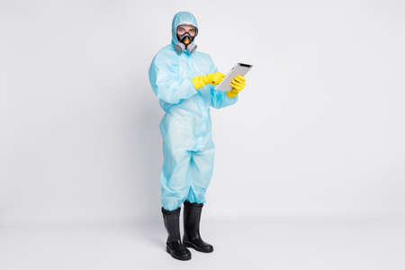 Full size photo of smart doctor man use tablet search read social media ncov epidemic information wear white suit hazmat latex gloves boots breathing mask isolated gray color background