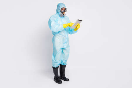 Full length photo of focused doctor man use tablet search covid19 information statistics wear white yellow suit hazmat breathing mask isolated over gray color background