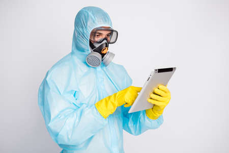 Photo of focused man use tablet search covid epidemic outbreak information texting typing social media wear white suit hazmat latex gloves breathing mask isolated gray color background