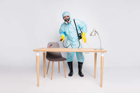Full length photo of professional cleaner man in bio white hazard wash disinfect office desk use sprayer equipment isolated over gray color background