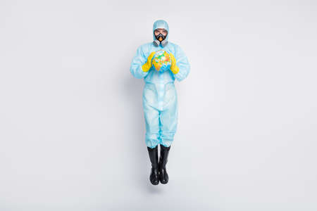 Full length photo clean hygiene man jump hold globe stop international ncov epidemic outbreak wear white suit hazmat yellow rubber latex gloves glasses goggles isolated gray color background
