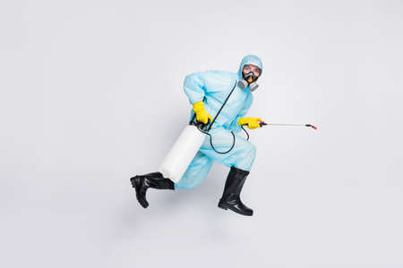 Full size profile side photo man jump run use sprayer hurry disinfect house wear white suit hazmat yellow rubber latex gloves goggles breathing mask isolated gray color background