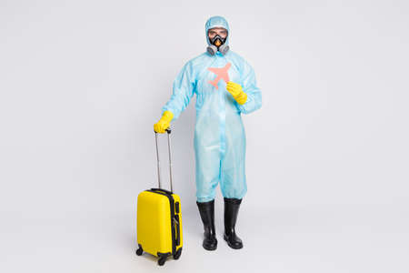 Full size photo man hold bag paper card plane no relax travel ncov quarantine wear white suit hazmat yellow rubber gloves glasses goggles breathing mask isolated over gray background Reklamní fotografie