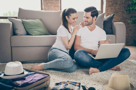 Photo of charming lady handsome guy friendly couple stay home sit floor packing stuff clothes planning trip after quarantine buy laptop online reservation low price tickets room indoors