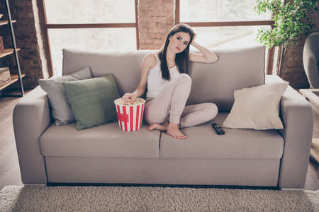 Full length photo of frustrated bored girl sit divan watch uninteresting movie have pop corn box eat stay home in house indoors
