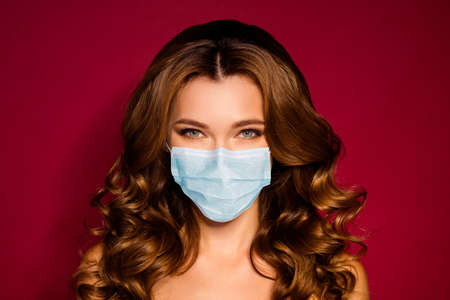 Closeup portrait of nice-looking attractive glamorous groomed perfect cheerful wavy-haired lady wear protective respiratory mask isolated bright vibrant red maroon marsala color background