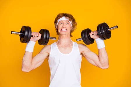 Close-up portrait of his he nice attractive funky self motivated guy sportsman lifting heavy barbell doing work out endurance isolated over bright vivid shine vibrant yellow color background