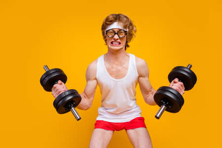 Portrait of his he nice attractive funky motivated guy sportsman lifting heavy barbell endurance hard regime plan isolated over bright vivid shine vibrant yellow color background