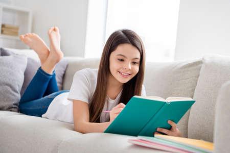 Foto der kleinen hübschen Schülerin Schuldame, die bequemes Sofa liest Tagebuch Buch positiv gute Laune fleißige Schülerin Notizen schreiben Bleistift soziale Distanz Quarantäne zu Hause lernen Komfortzimmer drinnen