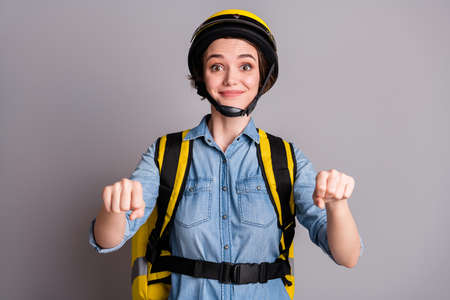 Portrait of positive courier girl biker drive imaginary scooter deliver cafeteria meal client customer wear denim jeans shirt helmet isolated over gray color background