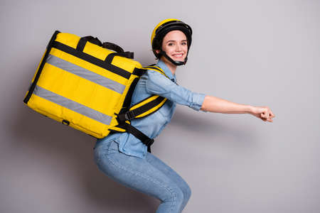 Profile side photo of positive girl courier drive scooter concept deliver client food meal pizza hold thermo backpack wear denim jeans shirt helmet isolated over gray color background