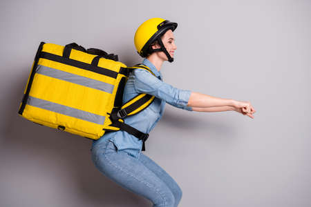 Profile side photo of positive courier girl drive motor bike concept deliver yellow package container client customer wear denim jeans shirt helmet isolated over gray color background