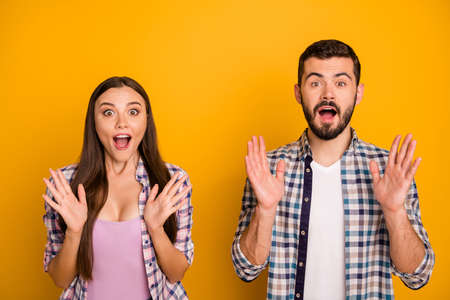Photo pretty lady handsome guy couple listen good news open mouth crazy facial expressions emotions raise arms wear casual plaid shirts outfit isolated yellow color background