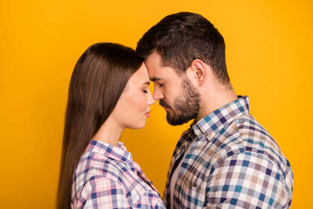 Closeup profile photo pretty lady handsome guy tenderness eyes closed leaning heads with love emotions stand close wear casual plaid shirts isolated yellow color background