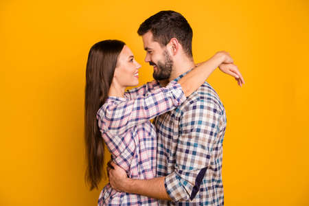 Profile side photo of trust positive spouses man woman hug embrace enjoy summer valentine day date together wear checkered plaid shirt isolated over bright shine color background