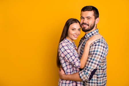 Portrait of dreamy passionate spouses hug embrace cuddle enjoy valentine day date copyspace wear checkered clothes isolated over bright shine color background Stock Photo