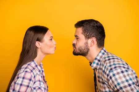 Profile side photo of passionate tender gentle two people man woman kiss copyspace enjoy valentine day holiday wear checkered plaid shirt isolated over bright shine color background