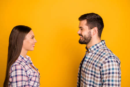 Profile side photo of affectionate couple man woman enjoy first sight appointment like each other wear checkered shirt isolated over bright shine color background