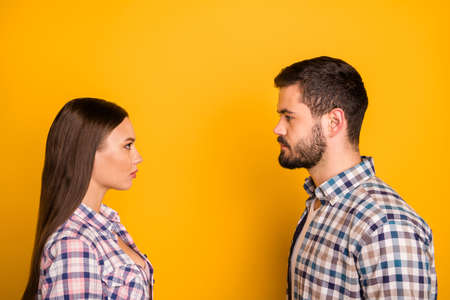 Closeup profile photo lady guy couple stand opposite keep distance not smiling look eyes responsible people citizens wear casual plaid shirts outfit isolated yellow color background