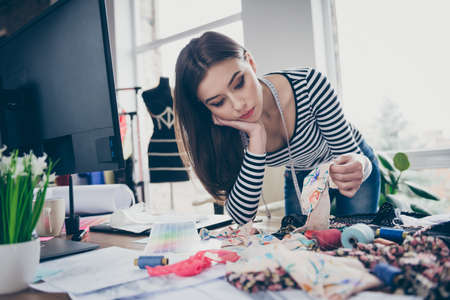 Close-up portrait of her she nice attractive lovely pretty focused tired bored seamstress needlewomen choosing materials garment design on table desk accessory at workplace workstation