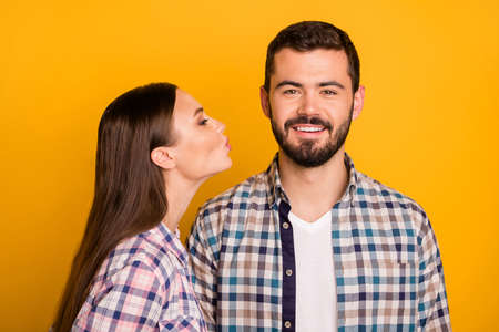 Portrait of passionate tender two people woman kiss man on 14-february date wear checkered plaid shirt isolated over bright shine color background